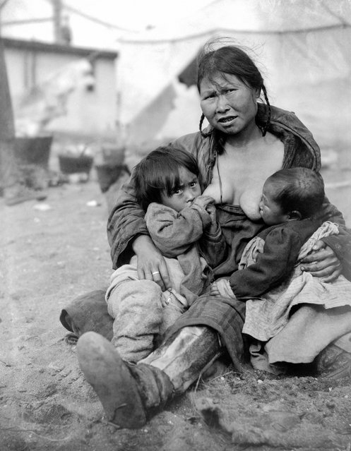 An Inuit Eskimo woman breast-feeding two babies, Alaska, 1904. (Photo by F.H. Nowell/Underwood Archives/Getty Images)