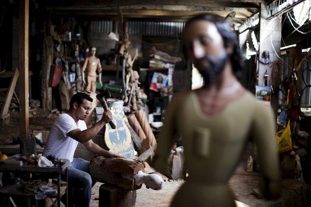 Jose Sabas Gomez's son Miguel Sabas works on a statue of El Jesus Nazareno in his workshop in Apastepeque, El Salvador March 9, 2016. (Photo by Jose Cabezas/Reuters)