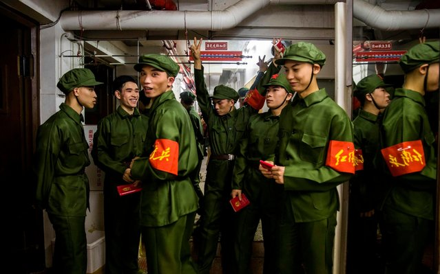 """Dancers dressed as People's Liberation Army (PLA) soldiers gather back stage during a rehearsal of a Cantonese opera called """"Trump on Show"""", in Hong Kong on April 11, 2019. In this absurd drama dubbed the """"Trump on Show"""", audiences will experience a fantastical mish-mash of current and historic events from the US President Donald Trump's meeting with North Korean leader Kim Jong Un to a fictional meeting with late Chinese leader Mao Zedong. (Photo by Isaac Lawrence/AFP Photo)"""