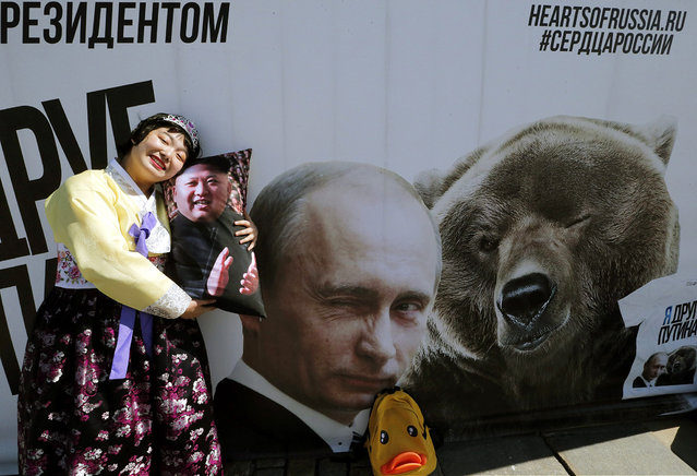 North Korean tourist poses with a souvenir pillow decorated with an portrait of Kim Jong-un in front of  a poster showing Vladimir Putin and a bear at the Victory park in Moscow, Russia, 08 May 2015. (Photo by Anatoly Maltsev/EPA)