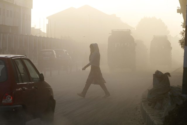 A Kashmiri woman covers her face as she crosses a dusty road in Srinagar, India, Wednesday, May 6, 2015. Air pollution kills millions of people every year, including more than 627,000 in India, according to the World Health Organization. The WHO puts 13 Indian cities in the world's 20 most polluted, with New Delhi deemed the filthiest, while pollution levels even in the countryside are often several times above what is deemed safe. (Photo by Mukhtar Khan/AP Photo)
