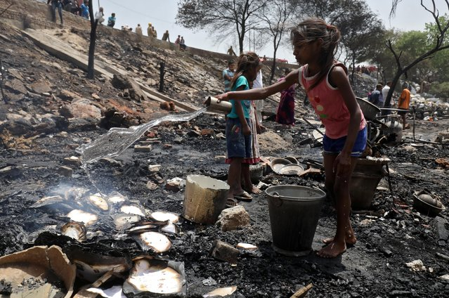 A girl throws water on burnt books after a fire at a slum in New Delhi, April 27, 2019. (Photo by Anushree Fadnavis/Reuters)