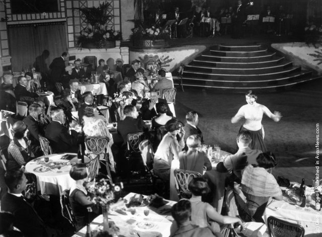Diners and a cabaret performer in the ballroom at Palm Beach Cafe on the Thames