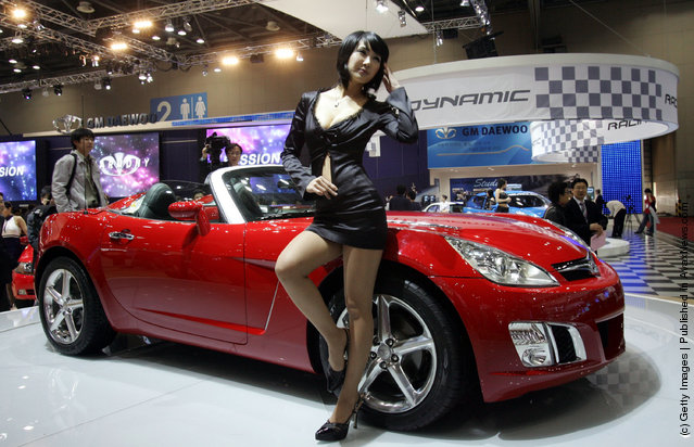 A Model poses next to a GM Daewoo Motor's Sport car at the Seoul Motor Show