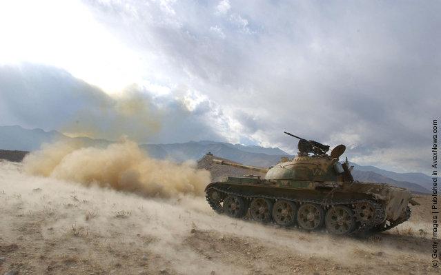 An anti-Taliban tank fires into the hills of Tora Bora
