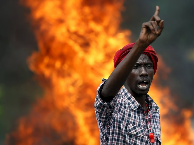 A protester gestures in front of a burning barricade during a protest against Burundi President Pierre Nkurunziza and his bid for a third term in Bujumbura, Burundi, May 21, 2015. (Photo by Goran Tomasevic/Reuters)