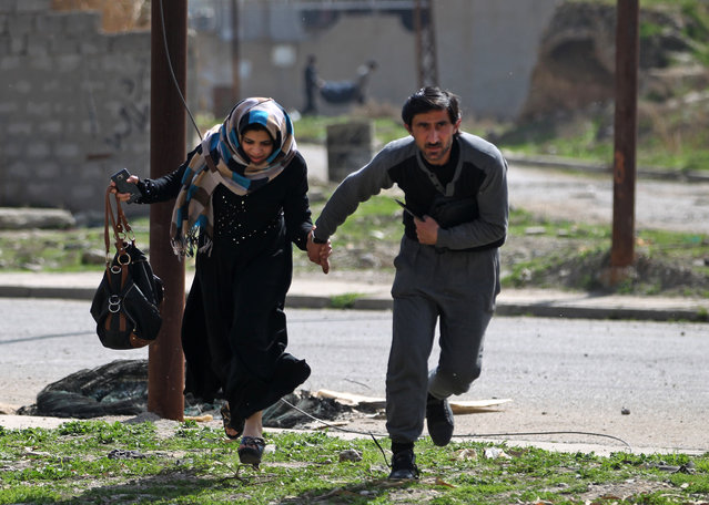 Iraqis run for cover as they flee Mosul's Al-Tayaran neighbourhood on February 28, 2017, during an offensive by Iraqi forces to retake the area from Islamic State (IS) group fighters. Hundreds of civilians fled through the desert to escape fighting and privation in Mosul, joining thousands of others who left their homes as conditions worsen in the city's west. (Photo by Ahmad Al-Rubaye/AFP Photo)