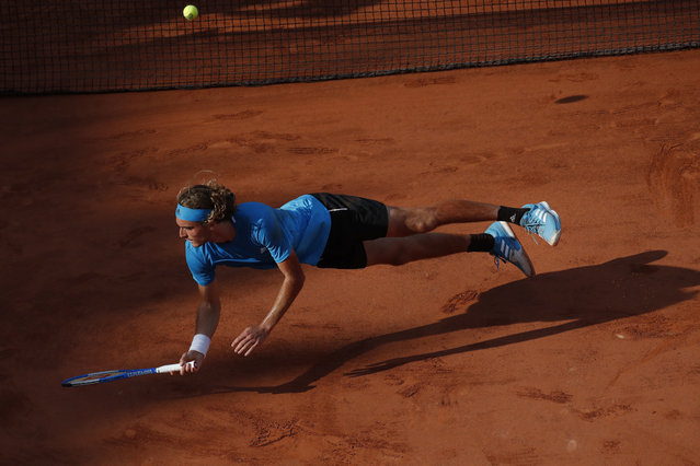 Greece's Stefanos Tsitsipas falls after diving to return a shot against Switzerland's Stan Wawrinka during their fourth round match of the French Open tennis tournament at the Roland Garros stadium in Paris, Sunday, June 2, 2019. (Photo by Christophe Ena/AP Photo)