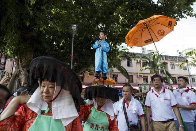 A boy, wearing a protective suit to depict a healthcare worker handling the bird flu, stands above the crowd with the support of a hidden steel rods on a float during a Bun Festival parade at Hong Kong's Cheung Chau island, China May 25, 2015. (Photo by Tyrone Siu/Reuters)