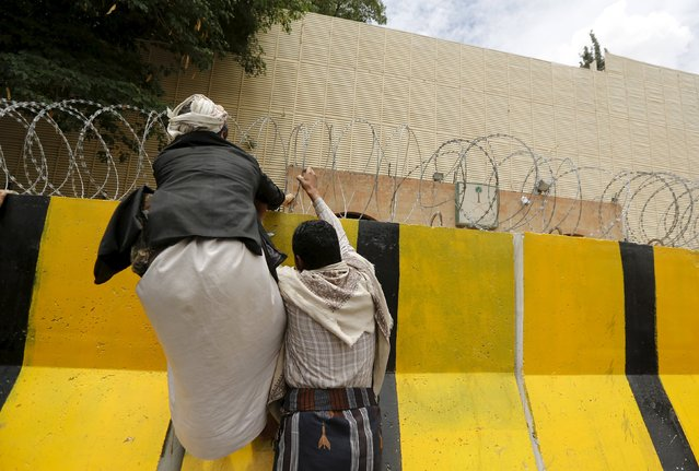 Houthi followers climb a barricade outside the Saudi embassy as they prepare to hang a banner against Saudi-led air strikes, in Sanaa May 25, 2015. (Photo by Khaled Abdullah/Reuters)