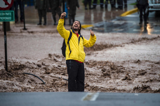 A man takes a selfie next to a flooded street due to the overflowing of the Mapocho river during heavy rains in Santiago on April 17, 2016. Four million people in Santiago were without tap water Sunday after unusually heavy rain pounding central Chile triggered landslides that fouled the city's water supply and forced the closure of the world's biggest copper mine, officials said. (Photo by Martin Bernetti/AFP Photo)