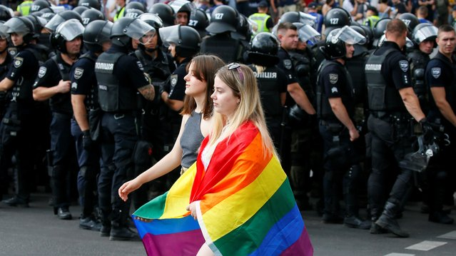 Police officers guard participants of the Equality March, organized by the LGBT community, in Kiev, Ukraine on June 23, 2019. (Photo by Gleb Garanich/Reuters)