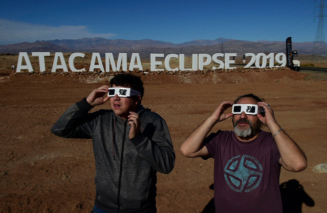 Tourists try special glasses to watch an eclipse at the entrance of an astronomical camp which expects to receive thousands of tourists to observe the July 2 total solar eclipse, in the commune of Vallenar in the Atacama desert about 600 km north of Santiago, on July 1, 2019. A total solar eclipse will be visible from small parts of Chile and Argentina on July 2. (Photo by Martin Bernetti/AFP Photo)