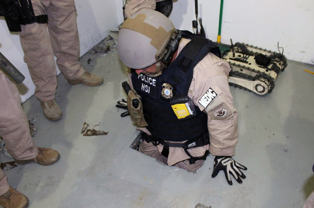 This image provided by the U.S. Immigration and Customs Enforcement (ICE) agency shows an agent examining one of two tunnels discovered April 1, 2014 in San Diego's Otay Mesa industrial park. The first tunnel, stretching about 600 yards, was discovered on Tuesday. Authorities say it was equipped with lighting, a crude rail system and wooden trusses. The other tunnel was discovered Thursday. It's described as stretching more than 700 yards and more sophisticated, with an electric rail system and ventilation equipment. (Photo by AP Photo/ ICE)