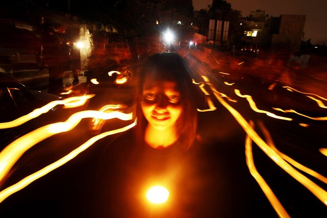 People hold candles during Earth Hour after the lights were turned off in central Amman. (Photo by Ali Jarekji/Reuters)