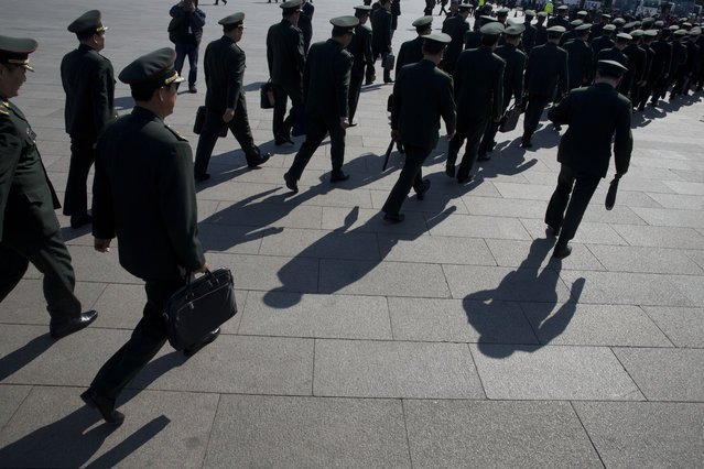 In this photo taken Wednesday, March 8, 2017, Chinese military officers file into near the Great Hall of the People where a plenary session of the National People's Congress is held in Beijing, China. (Photo by Ng Han Guan/AP Photo)