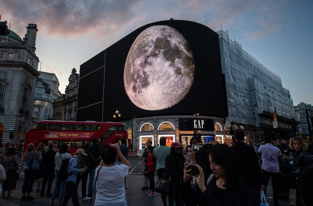 "Members of the public watch the ""People's Moon"" art installation on Picadilly advertising boards at piccadilly circus on July 20, 2019 in London, England. The ""People's Moon"" is being shown at Picadilly Circus during the precise hour that man landed on the moon 50 years ago. It is comprised of video clips and a mass of photos stitched together to create the surface of the moon. (Photo by Chris J. Ratcliffe/Getty Images)"