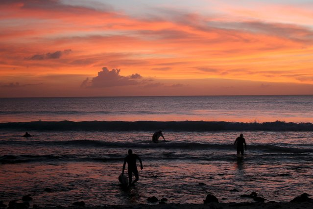 Surfers walk out of the water at sunset after surfing along the coast of Kiritimati Island, part of the Pacific Island nation of Kiribati, April 5, 2016. (Photo by Lincoln Feast/Reuters)