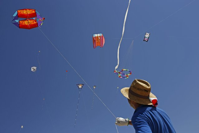 A man flies a kite during the 13th International Kite Festival at the Moinhos beach in Alcochete near Lisbon, Portugal, June 28, 2015. (Photo by Hugo Correia/Reuters)