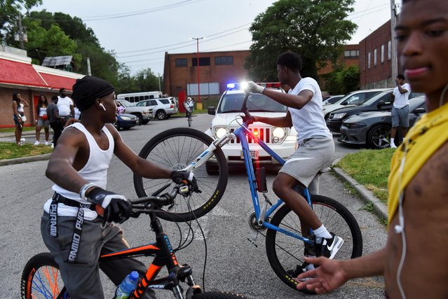 Young people ride their bikes near a police car while they gather in the parking lot of Hip Hop Chicken in Baltimore, Maryland, U.S., May 26, 2019. Each Sunday the bikers gather to ride their bikes and hang out in a loosely affiliated group of bikers. (Photo by Stephanie Keith/Reuters)