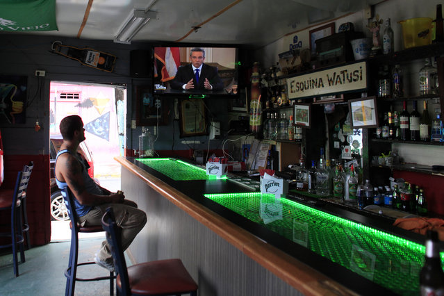 A man in a local bar watches Puerto Rico's governor Alejandro Garcia Padilla on television delivering an address on the state of the island's finances, in San Juan, Puerto Rico, Monday, June 29, 2015. The governor said that he will form a financial team to negotiate with bondholders on delaying debt payments and then restructuring $72 billion in public debt that he says the island can't repay. (Photo by Ricardo Arduengo/AP Photo)