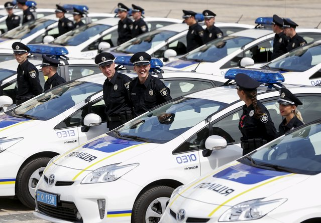 Police officers stand amidst cars before an oath-taking ceremony, which started up the work of a new police patrol service, part of the Interior Ministry reform initiated by Ukrainian authorities, in Kiev, Ukraine, July 4, 2015. (Photo by Valentyn Ogirenko/Reuters)