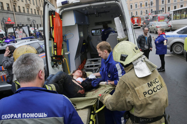 An injured person is helped by emergency services outside Sennaya Ploshchad metro station, following explosions in two train carriages at metro stations in St. Petersburg, Russia April 3, 2017. (Photo by Anton Vaganov/Reuters)