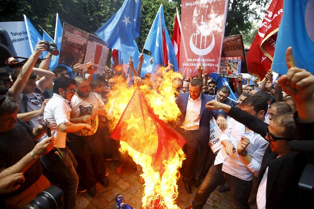 "Demonstrators set fire to a Chinese flag during a protest against China near the Chinese Consulate in Istanbul, Turkey, July 5, 2015. China warned its citizens travelling in Turkey to be careful of anti-Beijing protests, warning them that some Chinese tourists have recently been ""attacked and disturbed"". (Photo by Osman Orsal/Reuters)"