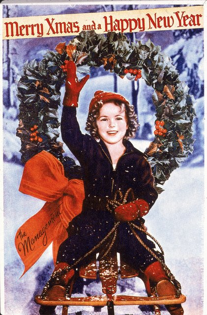 Christmas card or promotional portrait of American child actress Shirley Temple, who rides on a sled and waves, 1930s
