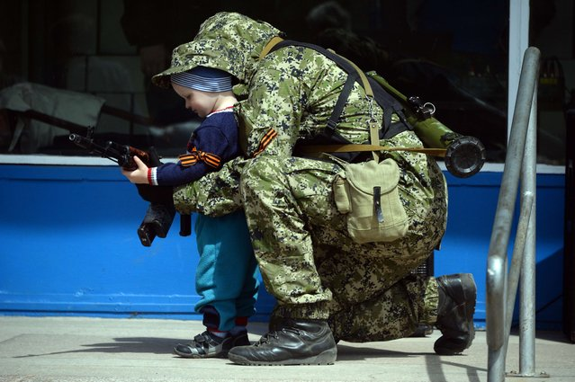 A pro-Russian armed man in military fatigues poses for a photograph with a child as he stands guard outside a regional administration building seized in the night by pro-Russian separatists, in the eastern Ukrainian city of Kostyantynivka, on April 28, 2014. The United States moved to impose fresh sanctions against Russia today over the crisis in Ukraine, as pro-Kremlin gunmen seized another town in the east, further escalating tensions. (Photo by Vasily Maximov/AFP Photo)
