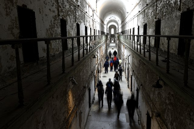 """A tour group wanders through block 7 of Eastern State Penitentiary in Philadelphia, Pennsylvania April 30, 2014. Opened in 1829, with the original corrective system of """"confinement in solitude with labor"""", the penitentiary housed about 75,000 inmates in its 142 years of operation. At Eastern State reunions, former inmates, staff and guard gather to share memories and trade stories and get a chance to describe their experiences in question-and-answer sessions with the public. (Photo by Mark Makela/Reuters)"""