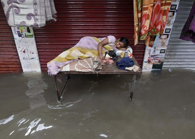 A mother rests with her child on a table in front of a closed shop in a flooded street after heavy rainfall in Kolkata, India, July 10, 2015. After drenching India with above-average rains in June, the monsoon has weakened in what is typically the wettest and most crucial month for millions of farmers growing oilseeds, rice, cotton and pulses. (Photo by Rupak De Chowdhuri/Reuters)