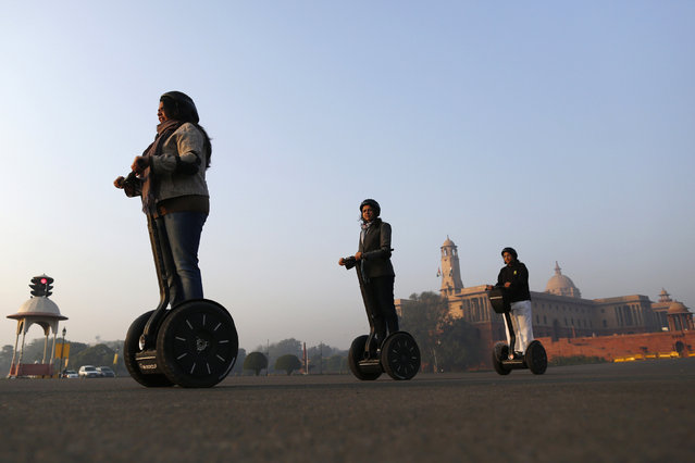 Women ride two-wheeled self-balancing scooters past the Indian Defence Ministry, in New Delhi December 5, 2013. (Photo by Anindito Mukherjee/Reuters)