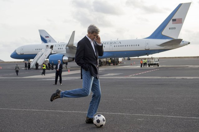 U.S. Secretary of State John Kerry kicks a soccer ball while talking on his cellphone during an airplane refuelling stop, while enroute to Washington, at Sal Island, Cape Verde, May 5, 2014. (Photo by Saul Loeb/Reuters)