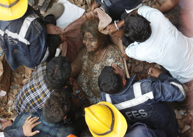 Rescuers carry a survivor at the site of a collapsed residential building in Ahmedabad, India, September 5, 2019. (Photo by Amit Dave/Reuters)