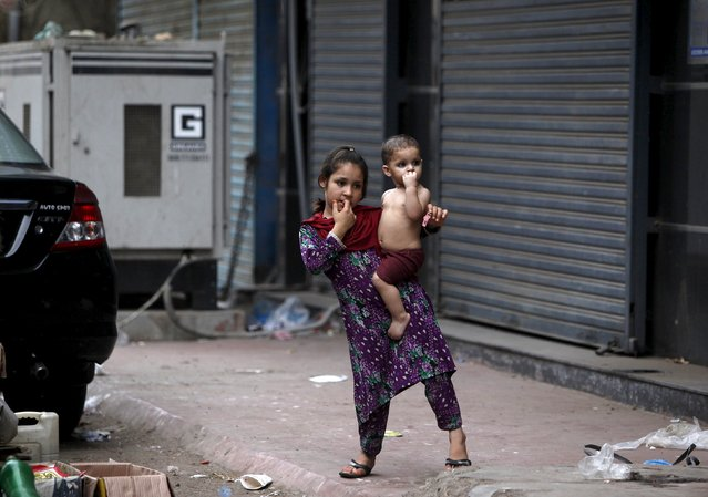A Pashtun girl carries her sibling while standing near her family home during a power outage in Karachi, Pakistan, July 5, 2015. (Photo by Akhtar Soomro/Reuters)
