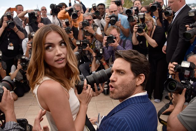 """Ana de Armas  uses a photographer's camera as Edgar Ramirez looks on during the """"Hands Of Stone"""" photocall during the 69th annual Cannes Film Festival at the Palais des Festivals on May 16, 2016 in Cannes, France. (Photo by Clemens Bilan/Getty Images)"""