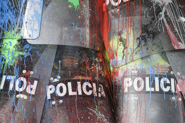 The shields of National Police are covered in paint thrown by protesting students in Bogota, Colombia, Thursday, October 10, 2019. Students are demanding more government resources for education and higher quality universities. (Photo by Ivan Valencia/AP Photo)