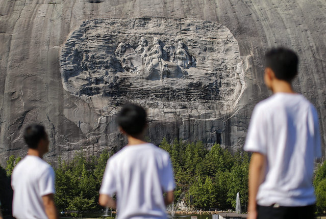 """Visitors view the Confederate Memorial Carving, depicting three Confederate heroes of the US Civil War, President Jefferson Davis (L), General Robert E. Lee (C) and Thomas J. """"Stonewall"""" Jackson (R) on Stone Mountain in Stone Mountain, Georgia, USA, 15 July 2015. The Atlanta chapter of the National Association for the Advancement of Colored People (NAACP) has called for the elimination of all Confederate symbols from the state-owned Stone Mountain Park, including the 27.5-meter-high, 58-meter-wide sculpture. (Photo by Erik S. Lesser/EPA)"""