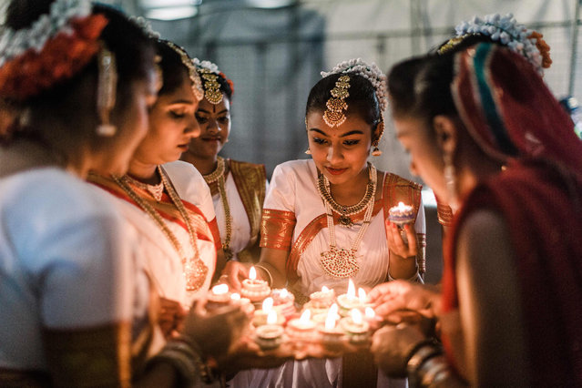A group of colourful dancers from the Kumari Shiksha Dance Institution light colourful clay lamps in preparation to celebrate Diwali during the two day Diwali (Festival of Lights) Hindu festival celebrations at the old Drive-Inn in Durban, on October 19, 2019. The two-day festival attracts over 100,000 visitors. The festival celebrations include, parading of floats, chariots, singing of devotional songs, dances, games, face painting, food stalls of vegetarian food, clothing, display of toys and jewellery. Young people also get the opportunity to showcase their cultural and spiritual talents. A billion Hindus worlwide will officially celebrate Diwali on 27 October 2019. (Photo by Rajesh Jantilal/AFP Photo)