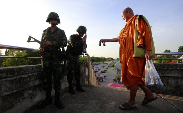A Buddhist monk offers energy drink to Thai soldiers guarding a pedestrian overfly near the site where pro-government demonstrators stage a rally on the outskirts of Bangkok, Thailand Tuesday, May 20, 2014. As Thailand finishes its first day under martial law, there are some questions that the military action raises. Many wonder if the arrival of soldiers in the streets of Bangkok constitutes a military coup, and how it affects people living in the Thai capital or visiting. (Photo by Wason Wanichakorn/AP Photo)