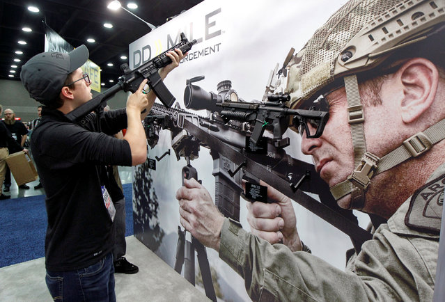 Sam Love looks over guns from Daniel Defense at the National Rifle Association's annual meetings and exhibits show in Louisville, Kentucky, May 21, 2016. (Photo by John Sommers II/Reuters)