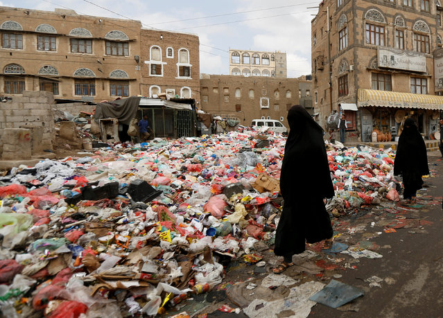 Women walk past a pile of rubbish bags on a street during a strike by garbage collectors demanding delayed salaries in Sanaa, Yemen May 8, 2017. (Photo by Khaled Abdullah/Reuters)