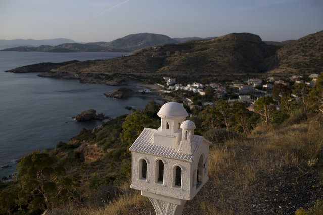 In this photo taken on Thursday, May 2, 2017, a roadside shrine stands near the sea at Cape Sounion, southeast of Athens. (Photo by Petros Giannakouris/AP Photo)