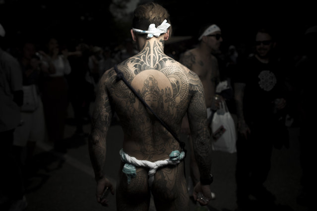 """In this picture taken on May 20, 2017, a man poses for photographs showing his """"Irezumi"""" Japanese traditional tattoos related to the Yakuza's universe, during the Sanja Matsuri festival in Tokyo. (Photo by Fred Dufour/AFP Photo)"""