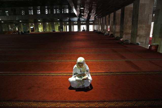 A Muslim woman reads the Quran following noon prayers on the first day of the holy fasting month of Ramadan at Istiqlal Mosque in Jakarta, Indonesia, Monday, June 6, 2016. (Photo by Tatan Syuflana/AP Photo)