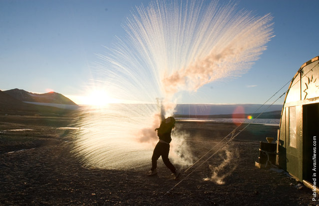 Long Term Ecological Research (LTER) field team member Anna Bramucci throws hot water into the air to watch it turn to ice crystals and vapor on a -25 F (-32 C) day at Lake Fryxell field camp in Taylor Valley, Victoria Land on March 30, 2008