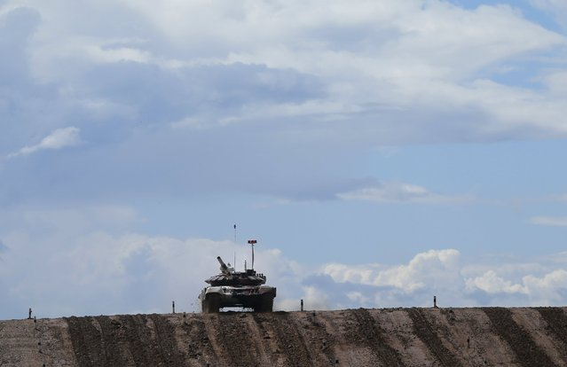A tank drives on the course of the Tank Biathlon competition during an opening ceremony of the International Army Games-2015 in Alabino, outside Moscow, Russia, August 1, 2015. (Photo by Maxim Shemetov/Reuters)