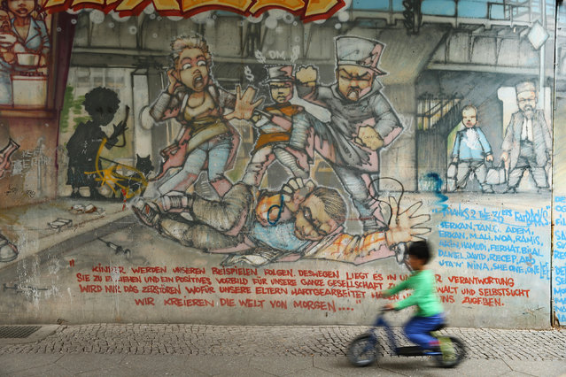 A boy on a bicycle rides past street art on the wall of an apartment building in Skalitzer Strasse in Kreuzberg district on June 26, 2014 in Berlin, Germany. Berlin, with its long tradition of counter-culture, has become a mecca for street art of all dimensions and messages. (Photo by Sean Gallup/Getty Images)