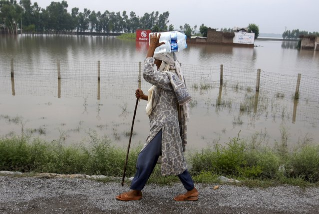 A woman carries water bottles as she walks at Camp Koruna flooded area of Nowshera District, northwestern Pakistan, August 3, 2015. (Photo by Khuram Parvez/Reuters)